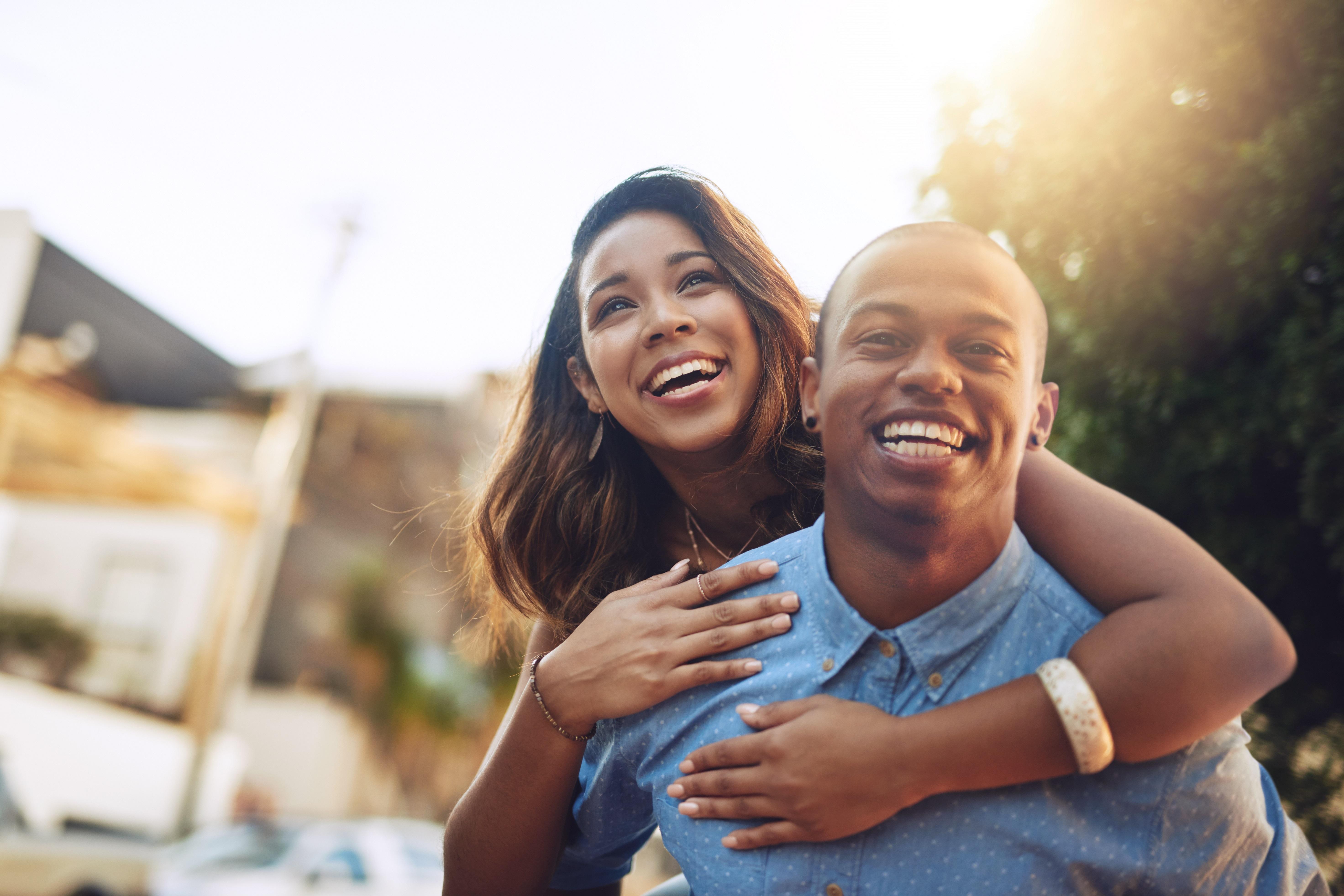 A happy young couple enjoying a piggyback ride outdoors